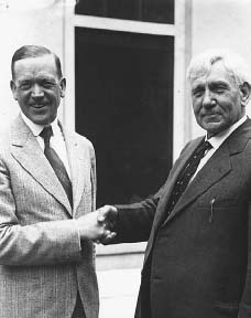 Senator Charles McNary (left) and Representative Gilbert Haugen shake hands after President Hoover signed a modified version of the McNary-Haugen Bill, shortly after succeeding Coolidge in the oval office. THE LIBRARY OF CONGRESS.