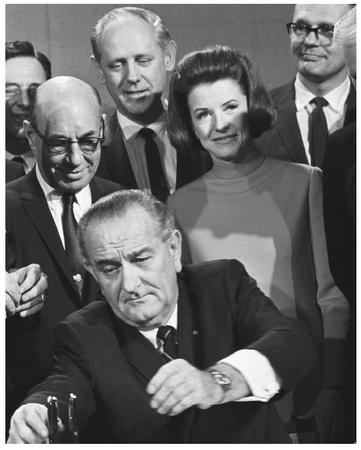 President Lyndon B. Johnson, surrounded by advisors and staff, signing a consumer bill.