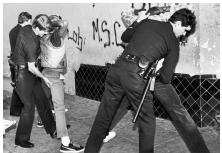 Los Angeles police officers search suspected members of the Rolling 60s gang for weapons and drugs during a sweep in south Los Angeles, March 31, 1985. (Bettmann/CORBIS)