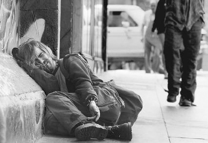 A young alcoholic man is shown lying against a building on a busy street in California. He cries as he begs for money to feed his addiction. His drinking habit has caused cirrhosis of the liver. AP/Wide World Photos.