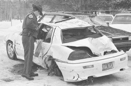 A Vermont state trooper examines a wrecked car that held four teens who died in a crash after a night of drinking in Canada. Some American teens go to Canada to drink because the legal drinking age is lower there. AP/Wide World Photos.