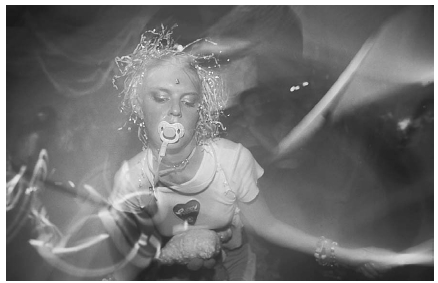 A young rave dancer is shown swirling lightsticks and sucking on a pacifier. Some rave dancers use pacifiers to keep them from grinding their teeth after taking ecstasy. Scott Houston/Corbis.