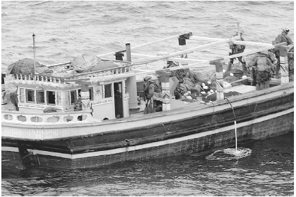 Members of the U.S. Navy and Marines inspect a small boat in the North Arabian Sea near the Persian Gulf in 2004. The military discovered more than 2,800 pounds of narcotics, including hashish, onboard. The raid was planned and carried out by U