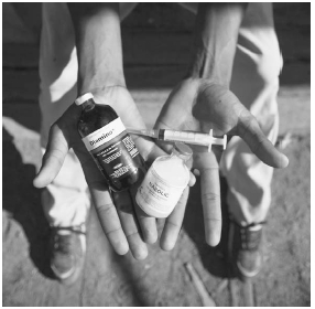 A teenage ballplayer in the Dominican Republic is shown holding two bottles of injectable drugs: a horse vitamin supplement and an animal steroid. Some aspiring ballplayers purchase the drugs, intended for animals, to bulk up and improve their