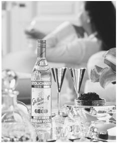 Aphrodisiacs flirt with the libido, and in this advertisement for vodka, the message is clear, yet subtle. Sparkling crystal, silver glasses, and caviar imply indulgent luxury, yet it is the glasses for two and the beautiful woman in the background that tells us that this intimate indulgence will also lead to love. PHOTO COURTESY OF STOLICHNAYA RUSSIAN VODKA.