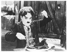 Charlie Chaplin in the 1925 movie The Gold Rush demonstrates the art of eating a boiled shoe. © BETTMANN/CORBIS.