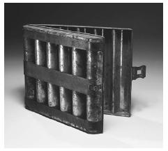 "As bread baking became industrialized during the nineteenth century, professional bakers turned to baking aids like this cream loaf pan of tinned sheet iron, which simultaneously makes six large sandwich ""batons."" The loaves are perfectly round for slicing. Manufactured about 1890 by Thomas Mills Brothers of Philadelphia. ROUGHWOOD COLLECTION. PHOTO CHEW & COMPANY."