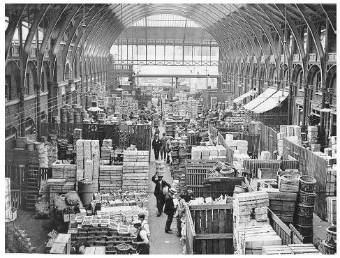 The interior of Covent Garden in London, circa 1920. This market hall was one of the largest in England as well as the center of London's food distribution system until after World War II, when it was closed due to traffic congestion. ROUGHWOOD COLLECTION.