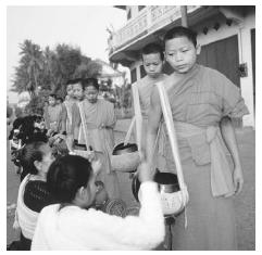 The kneeling women are giving donations of rice to a procession of monks in Luang Prabang, Laos, March 1993. The monks collect rice every morning. © MICHAEL S. YAMASHITA/CORBIS.