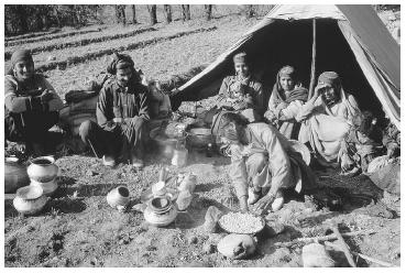 Bakarwal gypsy family preparing chapatis over a camp fire at Sonamarg, India. The Bakarwal gypsies are a nomadic group who travel between the Jammu lowlands of India and the mountains of Afghanistan. © LINDSAY HEBBERD/CORBIS.