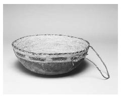 Traditional bowl made of grass fibers for milking camels. Oman, twentieth century. The handle and exterior covering are goat hide. ROUGHWOOD COLLECTION. PHOTO CHEW & COMPANY.