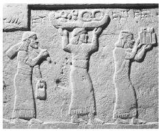 Bas-relief on the ancient Assyrian throne of Shalmaneser III depicting offering bearers carrying various items of food. Courtesy of the Iraq Museum, Baghdad.© GIANNI DAGLI ORTI/CORBIS.