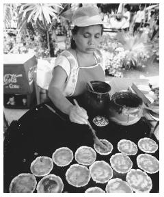 Woman preparing tortillas with salsa and beans in Mérida, Mexico. © ROBERT HOLMES/CORBIS.