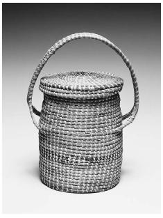 Gulla basket for storing dried okra. Made of long needle pine and reed grass in South Carolina, circa 1880. The hooplike handle was designed so that the basket could hang from a hook in the kitchen ceiling. This style of basket weaving was brought to South Carolina from West Africa. ROUGHWOOD COLLECTION. PHOTO CHEW & COMPANY.