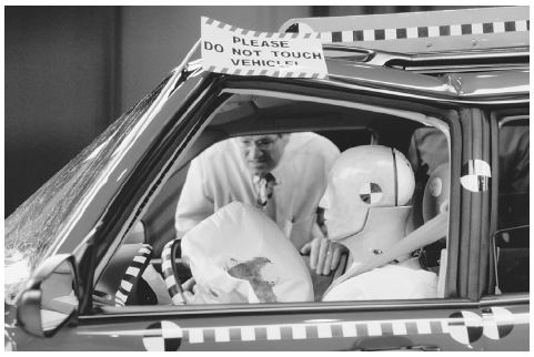 A researcher examines a crash dummy and deployed airbag after a test crash. A powdery substance helps many air bags deploy without sticking, and often leaves a residue that can be collected for evidence in a crash. TIM WRIGHT/CORBIS.