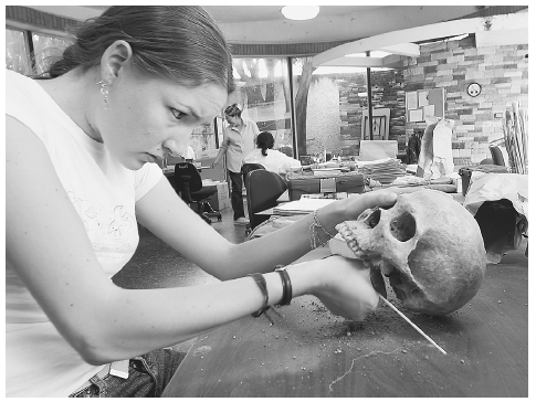 A member of the Guatemalan Forensic Anthropology Unit cleans a human skull in 2004 that was exhumed from a mass grave after a decades-long armed conflict in Guatemala left a toll of 500,000 people killed and 250,000 still missing. CARLOS LOPEZ