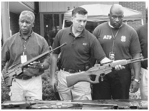 Three Bureau of Alcohol, Tobacco and Firearms (ATF) agents, from left, Walter Dandridge, Joe Anarumo and Steve Gerido, display rifles as examples of the type of guns that could have been used in the Maryland sniper shootings, Rockville, Marylan