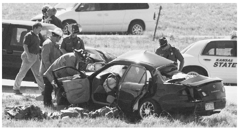 Kansas Highway Patrol troopers and Olathe firefighters work at the site of a fatal accident, near State Routes 10 and 7. AP/WIDE WORLD PHOTOS. REPRODUCED BY PERMISSION.