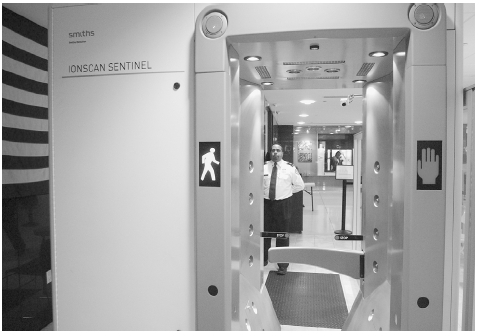 A security screener stands by a detection unit at JFK Airport in New York that provides explosive detection via a walk-through portal. The unit can detect particles and vapors of explosive materials by passing air over a person to release such