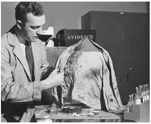 FBI lab technician cuts a sample of fabric from the clothing of a hit-and-run victim for comparison with fibers taken from the bumper of a suspects car. BETTMANN/CORBIS