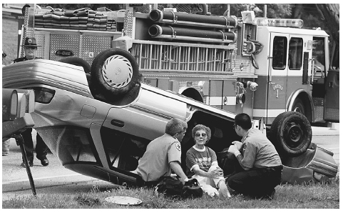 Emergency workers attend to an 80-year-old woman involved in a single-car accident which caused her car to flip onto its roof in Berlin, Vermont, on August 14, 1998. AP/WIDE WORLD PHOTOS. REPRODUCED BY PERMISSION.