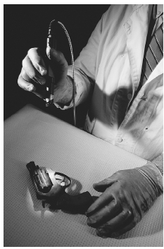 A technician at the San Francisco Police Department uses a laser to search for fingerprints on a gun. ED KASHI/CORBIS