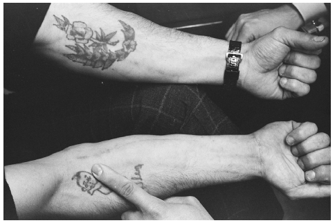 Tattoos on a heroin addicts arm, done for the purpose of covering up needle marks. TED STRESHINSKY/CORBIS