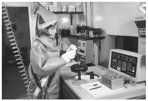 A Centers for Disease Control scientist wearing a protective suit with helmet and face mask is protected from pathogens as she conducts studies in the CDC BSL-4 laboratory. CDC/PHIL/CORBIS
