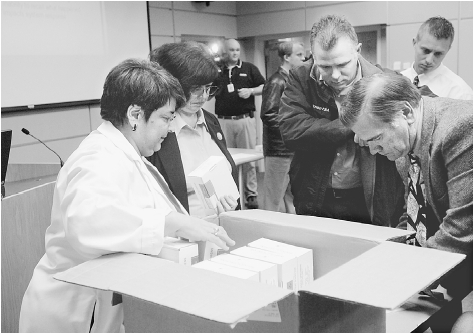 Head of the Connecticut State Police Forensic Laboratory hands out new kits for the collection of evidence in sexual assault investigations at the end of a training class in the use of the kits in October 2004. AP/WIDE WORLD PHOTOS. REPRODUCED