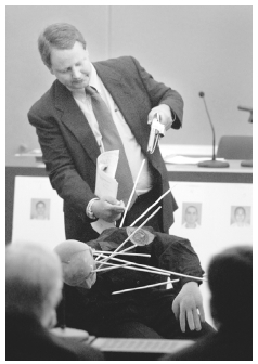 In a 2001 murder trial in Texas, a senior trace evidence analyst for the Institute of Forensic Sciences shows the direction from which bullets hit a police officer. AP/WIDE WORLD PHOTOS. REPRODUCED BY PERMISSION.
