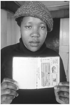 Under apartheid, black Africans had to have special permission to enter and remain within urban areas and were required to carry interior passports at all times. In this photo, a woman holds up the so-called dom pass. [ALAIN NOGUES/CORBIS SYGMA