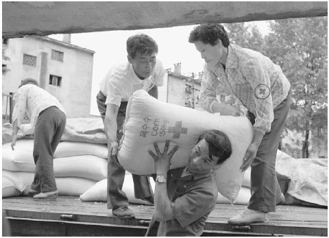 Widespread famine struck North Korea in 1995, but it was some time before a secretive government acknowledged the crisis and permitted relief efforts. In this August 10, 1997, photo, Red Cross workers unload bags of corn from a truck. [CORBIS]
