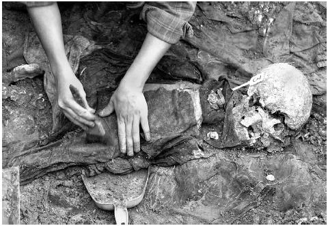 A forensic anthropologist cleans the remains of one of thirteen bodies found in a mass grave at a former army base in Chatalun, Guatemala, on December 19, 2000. About 5,000 Mayan Indians were rounded up by the Guatemalan army near Chatalun in D