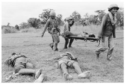 Cambodian troops dispassionately carry off the bodies of the dead. It has been estimated the Khmer Rouge annihilated some two million victims in their Killing Fields between 1975 and 1979. [AP/WIDE WORLD PHOTOS]