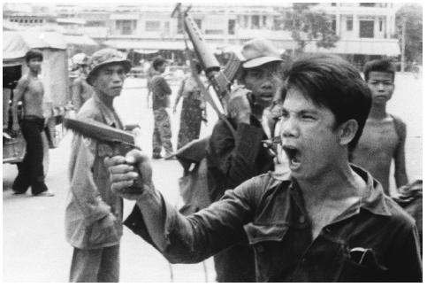 A Khmer Rouge soldier waves his pistol and yells orders in Phnom Penh, Cambodia, on April 17, 1975, as the capital fell to communist forces. [AP/WIDE WORLD PHOTOS]