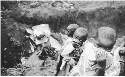 Rwandan children view a mass grave near Goma. [TEUN VOETEN]