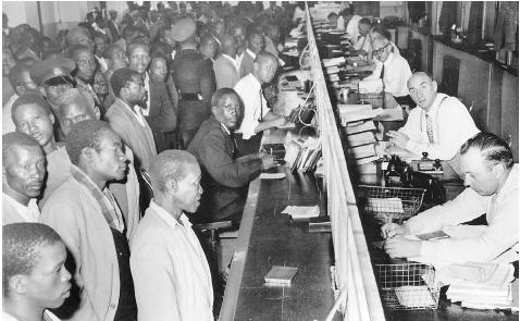The movement of black South Africans into and out of urban and employment centers was regulated by the Blacks Consolidation Act of 1945. These citizens of South Africa were required to carry special pass books at almost all times. In the photo,