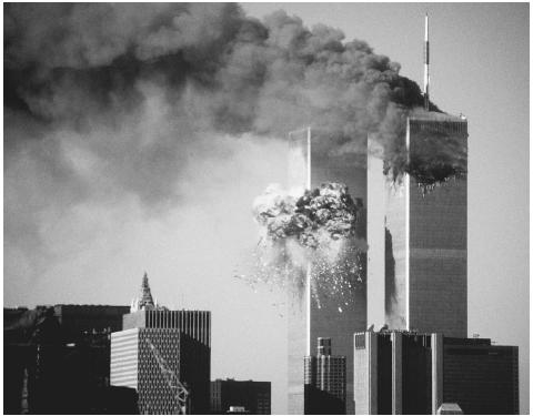 The South Tower of the World Trade Center explodes into flames after being hit by hijacked United Airlines Flight 175. The North Tower smolders following a similar attack some 17 minutes earlier. When both buildings, symbols of U.S. corporate m