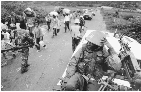 Under UN guard, Tutsis, carrying little more than food and a change of clothing, flee the Rwandan capital of Kigali. [TEUN VOETEN]