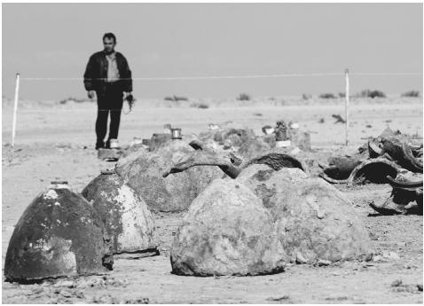 A bystander examines the rusted remains of Iraqi missile heads at Aziziyah, 90 kilometers south of Baghdad, February 27, 2003. Although the United States believed Saddam Husseins regime possessed weapons of mass destruction when it invaded Iraq
