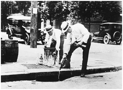 Federal agents pour whiskey into a sewer during Prohibition. Bettmann/Corbis.