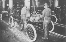 Workers install engines on Model Ts at a Ford Motor Company plant. The photo is from about 1917.