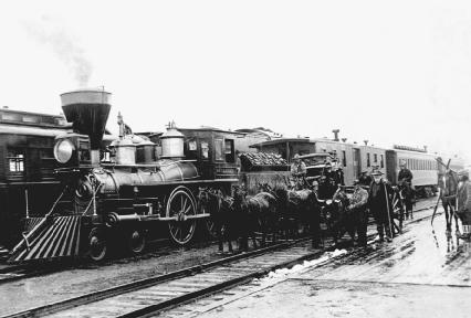 A steam train sits at a railway station. Many settlers desired land near railroads in the West to make shipping crops back east easier. © Corbis.
