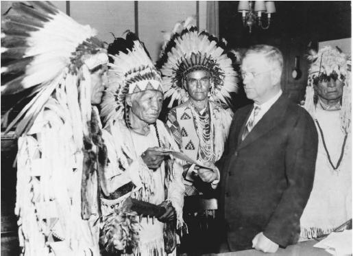 Secretary of the Interior Harold L. Ickes hands the first constitution issued under the Indian Reorganization Act to delegates of the Confederated Tribes of the Flathead Indian Reservation (Montana), 1935. (LIBRARY OF CONGRESS, PRINTS AND PHOTOGRAPHS DIVISION)