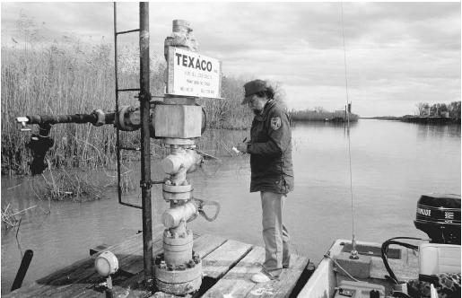 Oil and gas leasing, as authorized by the Mineral Leasing Act of 1920, in the Delta National Wildlife Refuge in Louisiana. Here, an employee of the U.S. Fish and Wildlife Service checks an oil well on the refuge. (© US FISH AND WILDLIFE SERVICE/PHOTO BY JOHN AND KAREN HOLLINGSWORTH)