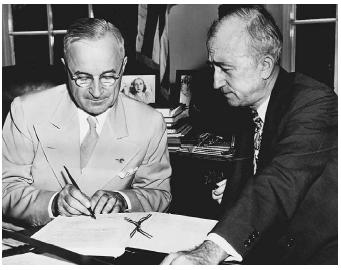 President Harry Truman signs a document ratifying the United Nations Charter, with Secretary of State James F. Byrnes by his side. The United Nations Participation Act gives the president authority to impose sanctions on a country as mandated by the U.N. Security Council, pursuant to Article 41 of the U.N. Charter. (©CORBIS)