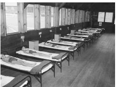 Young children lying on beds in a hospital ward.