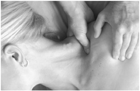 Therapist working acupressure points on a woman's shoulder. (Photo Researchers, Inc. Reproduced by permission.)