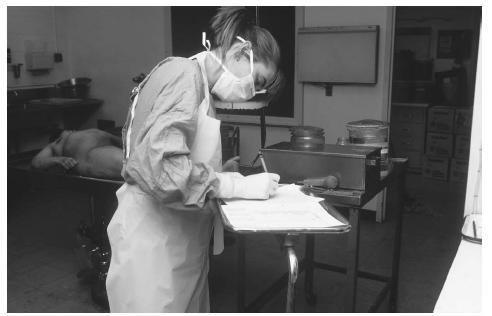 A pathologist fills out an autopsy report during an autopsy. (Photograph by Glauberman. Science Source/Photo Researchers. Reproduced by permission.)