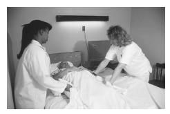 Two nurses change bedsheets with the patient in the bed. (Photograph by Cliff Moore. Science Source/Photo Researchers. Reproduced by permission.)